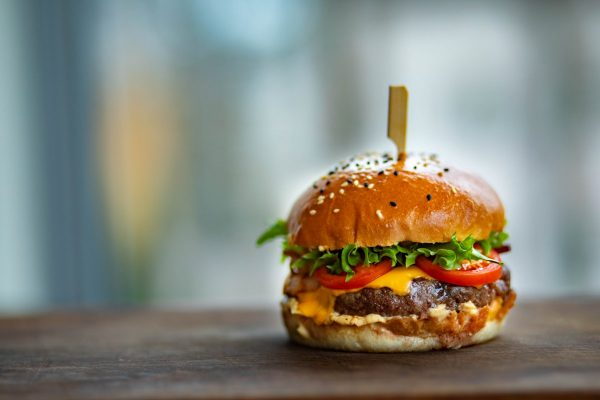 Photo of juicy burger on wooden surface