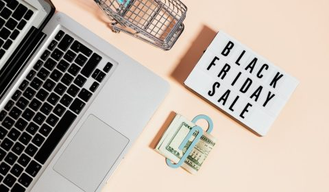 Top view of silver macbook beside a shopping cart and black friday sale signage