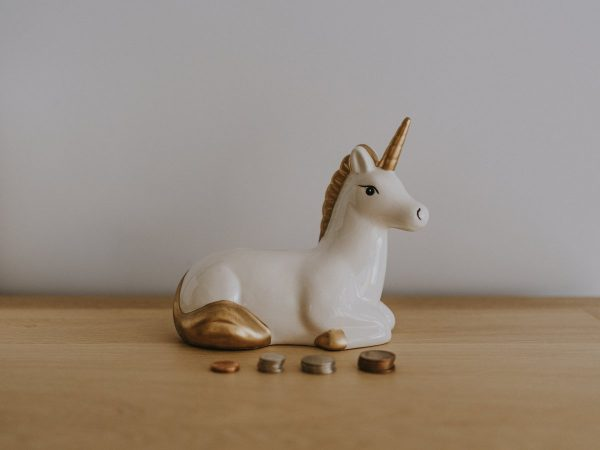 Unicorn money box and coins stacked