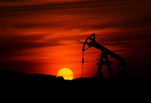 Pump-jack mining crude oil with the sunset