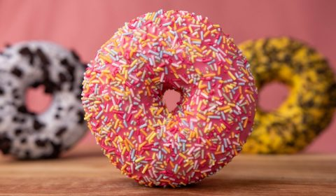 Doughnut with sprinkles on brown wooden table