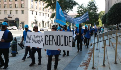 people standing on sidewalk holding blue and white banner