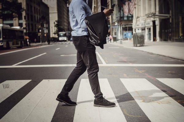 Crop stylish man walking on crosswalk in downtown