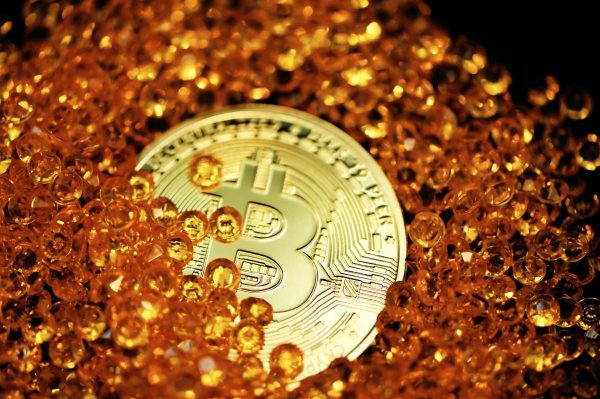 A single Bitcoin lays half buried by amber colored crystals.