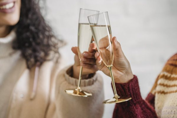 Friends clinking glass of champagne while celebrating occasion