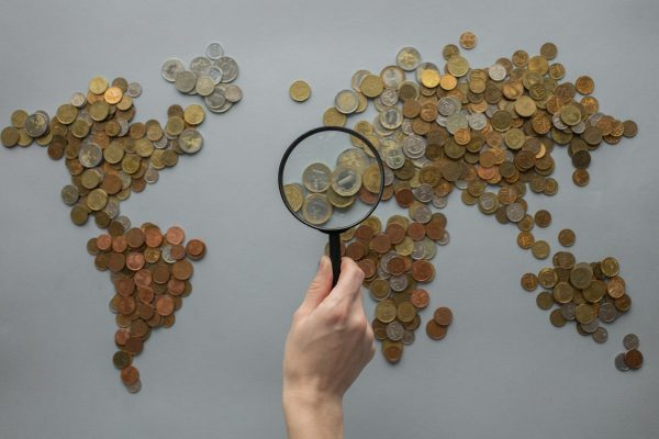 Anonymous person with magnifying glass over world map of coins