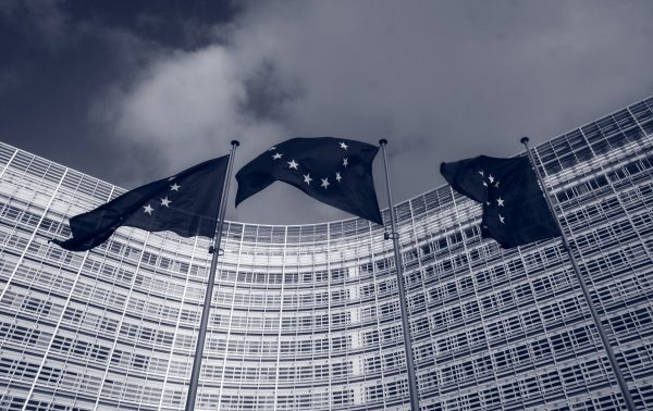 """Flags of the European Union in front of the EU-commission building """"Berlaymont"""" in Brussels, Belgium"""